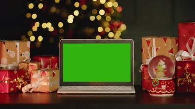 Laptop with Green Screen on Table with Christmas Decorations Against Christmas Tree
