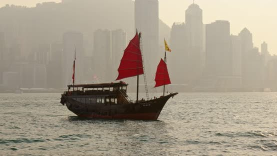 Thumbnail for Sunset skyline of Hong Kong with traditional cruise sailboat at Victoria harbor