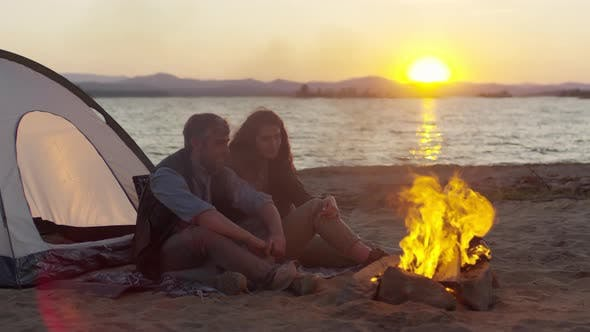 Thumbnail for Couple Looking at Campfire on Lake Beach
