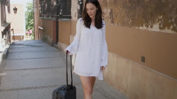 Thumbnail for Beautiful Woman Walking with Trolley Suitcase in Small Street in the City