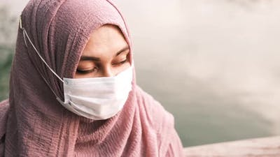 Thoughtful Muslim Woman with Flu Mask Looking Away