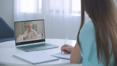 Female Student Study Online and Learns Video Lesson with Teacher Using Laptop at Home. E-learning