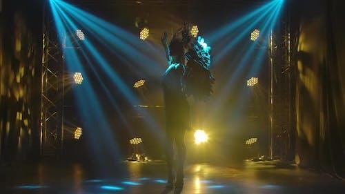 Eine junge Schauspielerin im Bild der griechischen Göttin Artemis posiert auf der Bühne in den Strahlen der Magischen