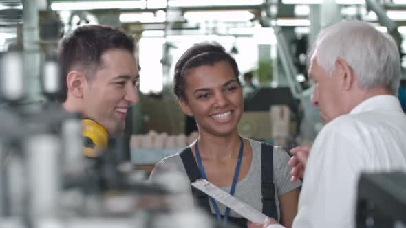 Cover Image for Cheerful Factory Workers Discussing Tasks