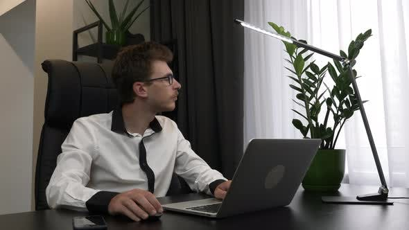 Thumbnail for Focused smart man in glasses is using laptop in modern office