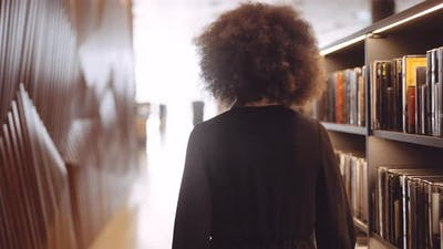 Young Woman Walking In Library