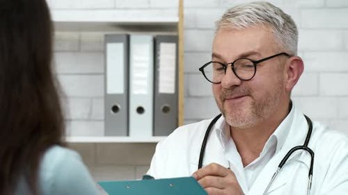 Professional Therapist Talking To Patient Woman Suggesting Treatment In Office