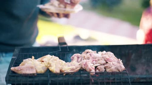 Close-up: Man Stands on the Background of a Summer House Lays Meat on a Barbecue Grill, Children Run