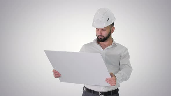Man Engineer Walking in Helmet Looking at Project of Reconstruction on Gradient Background.