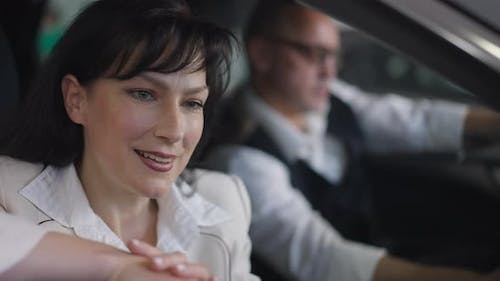 Charming Satisfied Wealthy Woman Admiring Luxurious Car Interiors Sitting with Man in Vehicle in