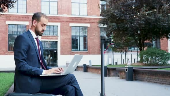 Thumbnail for Businessman Outdoor Typing on the Laptop Sitting in a Business District