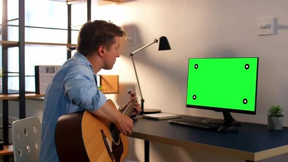 Young Man with Computer Playing Guitar at Home - product preview 0