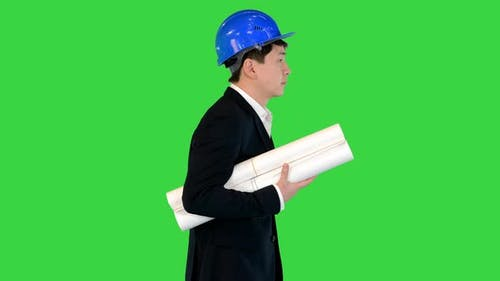 Asian Engineer with Blueprints Walking on a Green Screen Chroma Key
