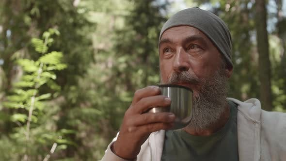 Porträt von gealterten Reisenden trinken Tee im Freien