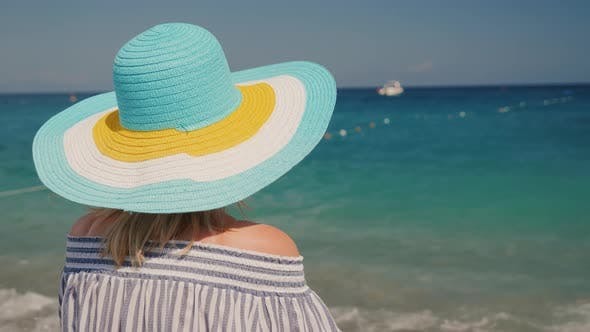Cover Image for A Young Girl in a Broad Hat of Bright Flowers Enjoying the Sea View on the Beach