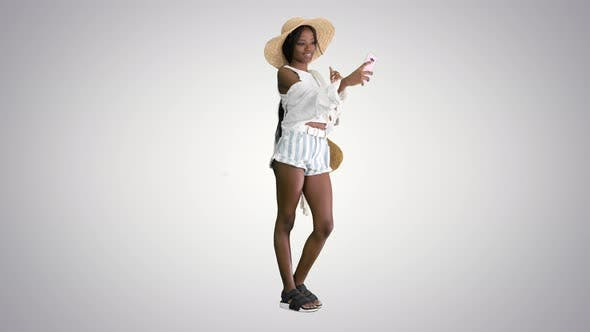 Smiling African American Woman Wearing Straw Hat and Taking Selfie on Smartphone on Gradient