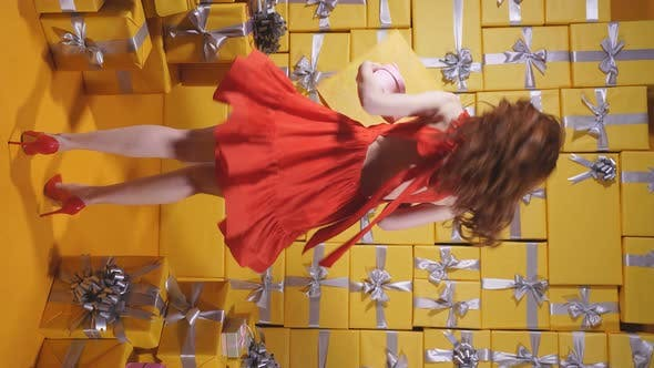 An Attractive Redhaired Young Woman in a Red Dress Enjoys Shopping Isolated By the Background of