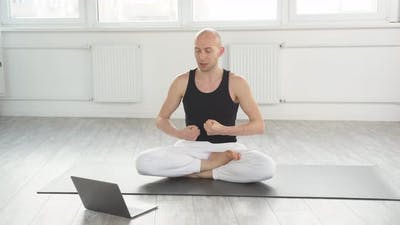 Yogi Male with Laptop Doing Yoga Teaching Students