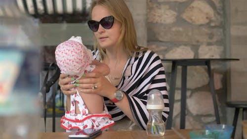 Jeune mère avec bébé fille au café