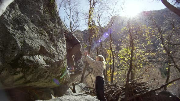 Thumbnail for Young woman spotting man as he climbs a boulder for sport