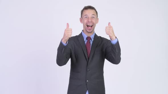 Thumbnail for Studio Shot of Happy Businessman Looking Excited While Giving Thumbs Up