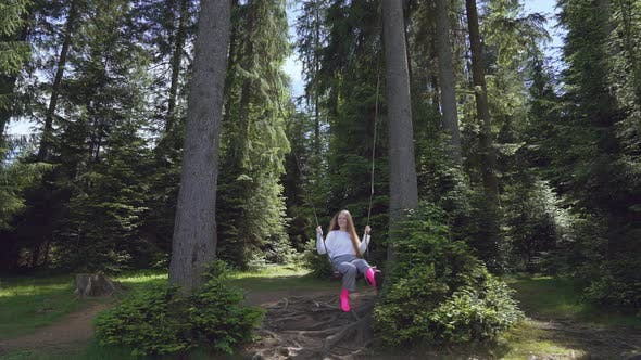 Thumbnail for Girl on Swing Between Trees in Forest