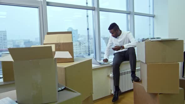 Thumbnail for Young African Manager Working on Window Sill after Moving in Office