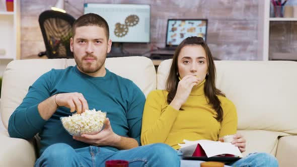 Cover Image for Scared Couple Watching Tv Eating Pizza and Popcorn Sitting on Couch