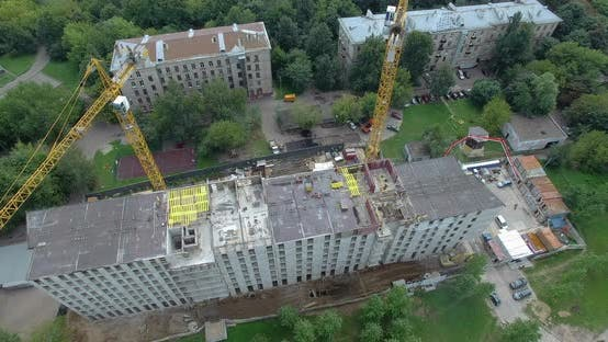 Aerial Shot of Workers and Cranes on Construction Site with Apartment Complex