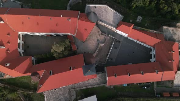 Aerial Top Down View of Medieval Castle on Mountain in Small European City at Cloudy Autumn Day