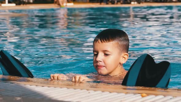 Thumbnail for Happy Boy with Flippers Swims in a Pool with Blue Water