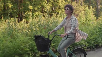 Cheerful Woman In Sunglasses Riding Bike Outdoors