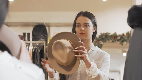 Beautiful Woman Trying on Hat at Fashion Store