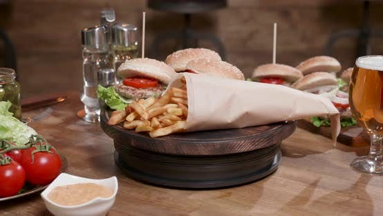 Delicious Composition of Fast Food Rotating on Wooden Board