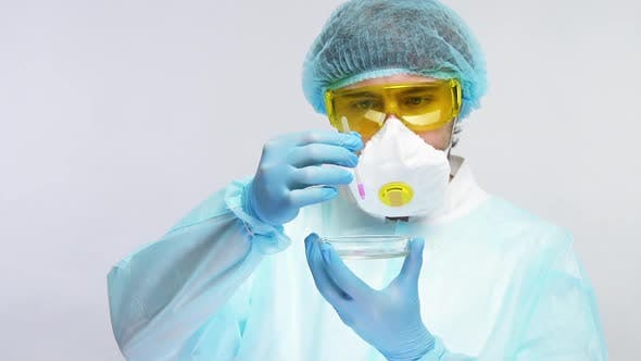 Thumbnail for Medical Chemist Holding Pipette with Pink Sample and Pouring It on Petri Dish