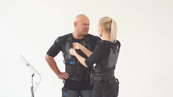 Cover Image for Fair-haired Girl Helps Man To Put on EMS Costume