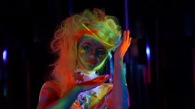 Beautiful Actress with Fluorescent Makeup is Posing for Camera at Darkness Medium Portrait Shot