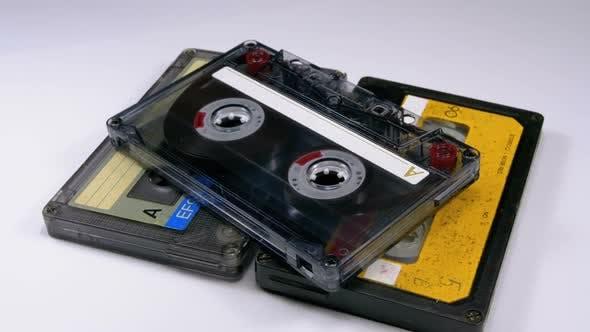 Three Vintage Audio Cassettes Rotate on White Background