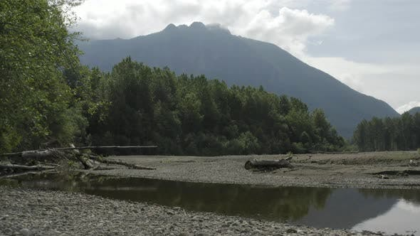 Cover Image for Flying Above Dried Up Snoqualmie River Majestic Gimbal Shot   Looming Mountain Background