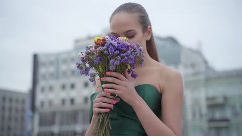 Beautiful Girl in Chic Dress Standing with Fragrant Bouquet of Wildflowers on the Background of the