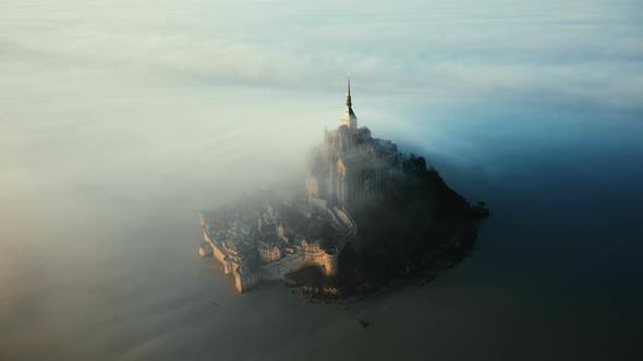 Epic Aerial Shot of Ethereal Mont Saint Michel Island Castle Covered with Amazing Sunrise Fog Clouds