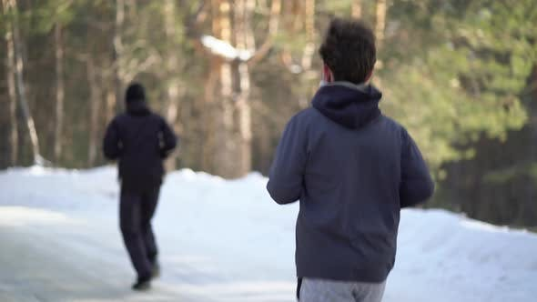 Young Male Athletes Jogging In Wintry Wood