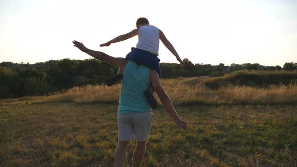 Thumbnail for Little Boy Sitting on the Shoulders of His Father and Playing Raised Hands As Airplane Outdoor. Dad
