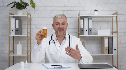 Mature Doctor Showing Tube With Medical Pills Sitting In Office