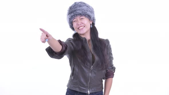 Cover Image for Happy Beautiful Asian Woman Pointing Finger and Ready for Winter