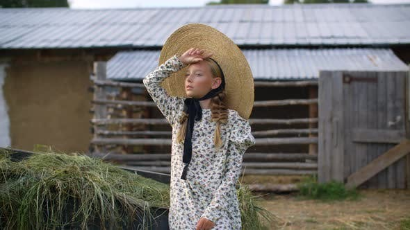 Thumbnail for Beautiful Girl with Two Braids in Hat and Romantic Dress Looking Away on Rural Landscape in