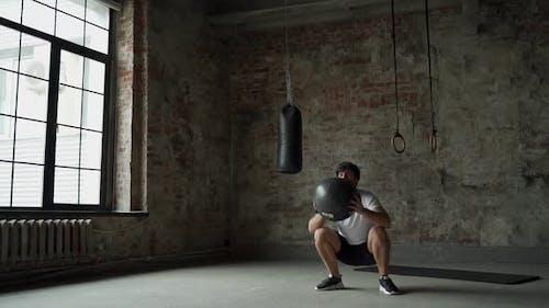 Athletischer Mann wirft medizinischen Ball im Fitnessstudio