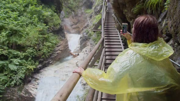 Cover Image for a Hiker in a Yellow Raincoat Taking Photo While Walking in a Mountain Canyon