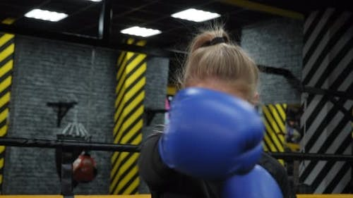 A Young Woman in Blue Boxing Gloves Practices Punches in the Boxing Ring
