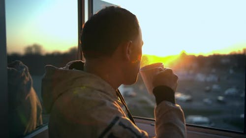 A young man in a sweatshirt drinks hot tea by the open window during a beautiful sunset